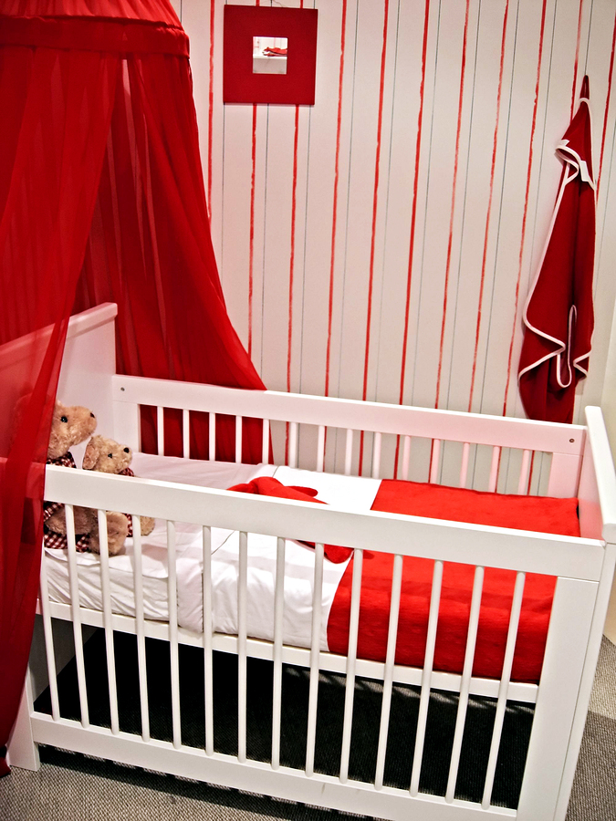 a baby room with red accents